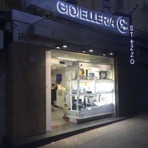 Insegna con fondo in plexiglass luminoso a led RGB, con applicazione di lettere in acciaio con ulteriore illuminazione.